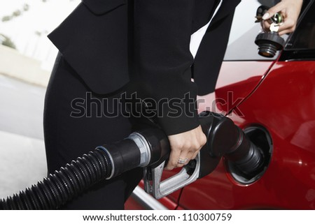 Woman refueling her car - stock photo