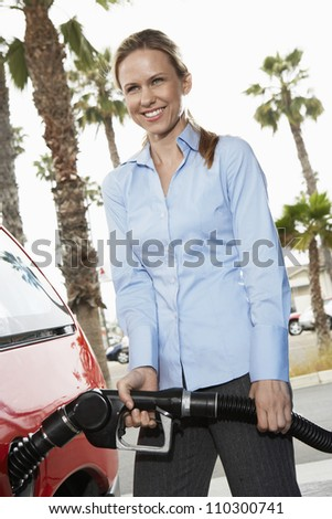 Woman refueling her car at a service station