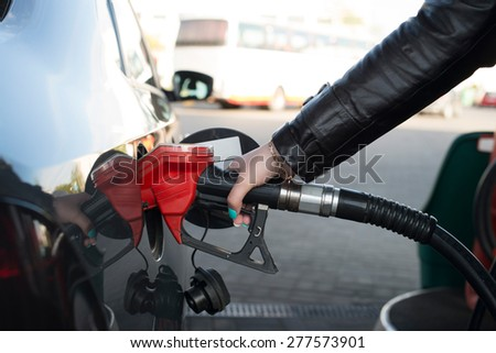 Woman refueling her car in a gas station - stock photo