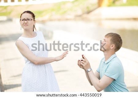 Woman refusing marriage proposal. Serious handsome young man standing on his knee offering box with engagement ring to girlfriend, asking to marry, waiting for answer. Girl turning away and saying no - stock photo