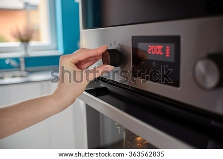 Woman regulates the temperature of the oven - 200C