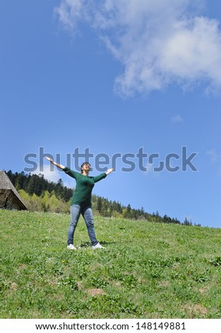Woman rejoicing in the sunshine standing in the middle of a green mountain field with her arms outspread towards the sun