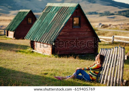 woman relax on grass at countryside. Wooden house and mountains background