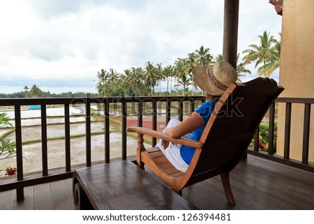 woman relaxed on chair looking on rice fields in Bali - stock photo