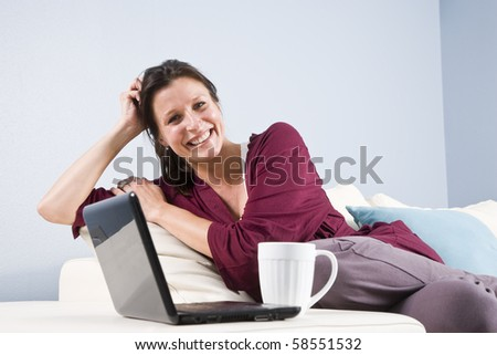 Woman relaxed on couch with laptop computer and coffee cup - stock photo