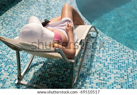 woman relaxes by the pool - stock photo