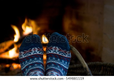 Woman relaxes by warm fire. Feet in woollen socks by the Christmas fireplace. Close up on feet. Winter and Christmas holidays concept.