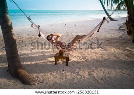 Woman relaxes in a hammock on a topical exotic beach - stock photo