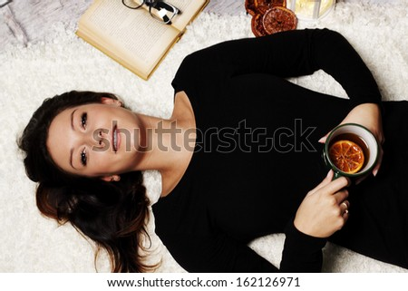 Woman relaxes with a cup of tea on a winter evening - stock photo