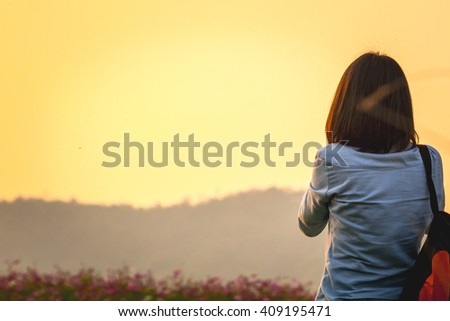 Woman relaxing against sunset. - stock photo