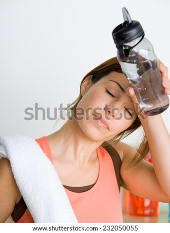 woman  relaxing and drinking water after a workout at the gym