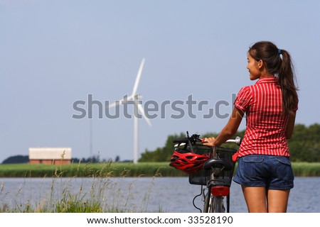 Woman relaxing and enjoying the sun on a bike trip in the countryside of Jutland, Denmark Windmill in the background. - stock photo