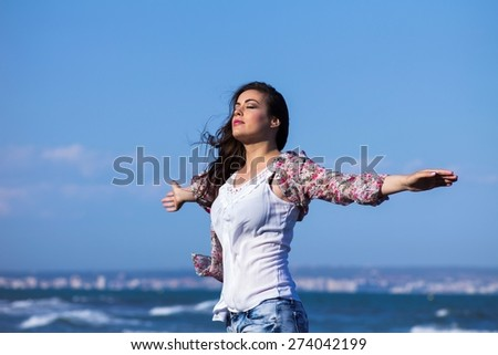 Woman relaxing at beach enjoying summer freedom with open arms and hair in the wind by the water seaside. - stock photo