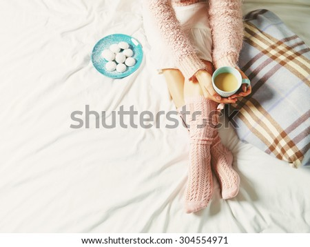 Woman relaxing at cozy home atmosphere on the bed. Young woman with cup of coffee or cocoa in hands and cookies enjoying comfort. Soft light and comfy lifestyle concept.  - stock photo
