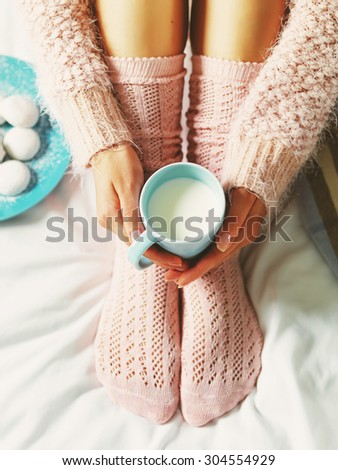 Woman relaxing at cozy home atmosphere on the bed. Young woman with cup of milk in hands and cookies enjoying comfort. Soft light and comfy lifestyle concept.  - stock photo