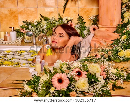 Woman relaxing at flower water spa. Luxury bathroom. - stock photo