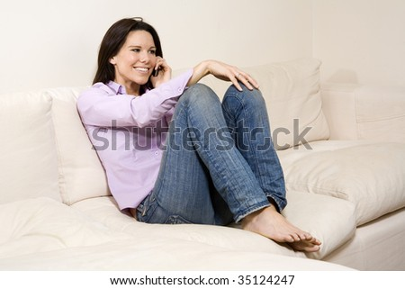 Woman relaxing at home, talking on her mobile phone""