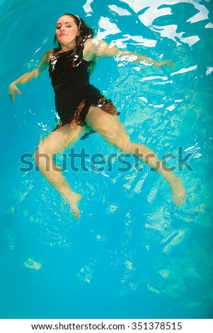 Woman relaxing at swimming pool. Young girl floating. Water aerobics fitness.