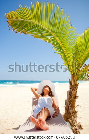 Woman relaxing at the beach enjoying her vacations - stock photo