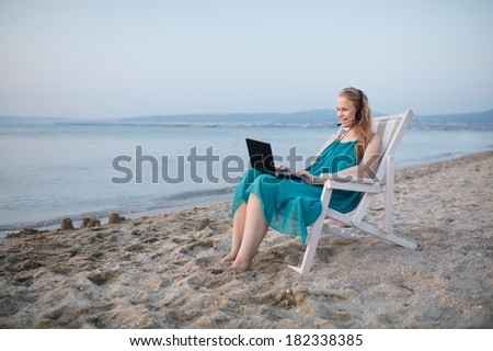 Woman relaxing at the beach in a deckchair alongside the ocean with her laptop computer and wearing a headset talking with her friend with skype