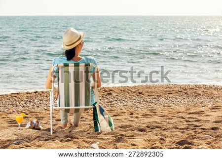Woman relaxing at the beach, sitting on a deck chair and enjoy the views of the sea - stock photo