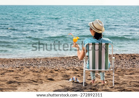 Woman relaxing at the beach, sitting on a deck chair and enjoy the views of the sea, drinking a cocktail - stock photo