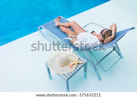 Woman relaxing at the swimming  pool reading a book on her holidays - stock photo