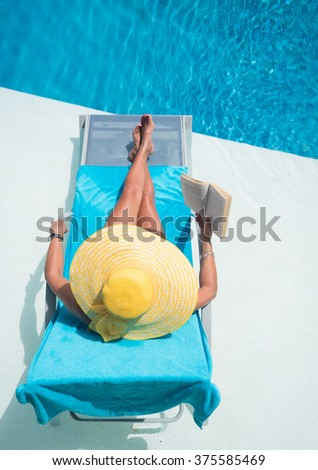 Woman relaxing at theswimming  pool reading a book - stock photo