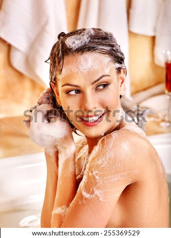 Woman relaxing at water in bubble bath. Girl looking to side.