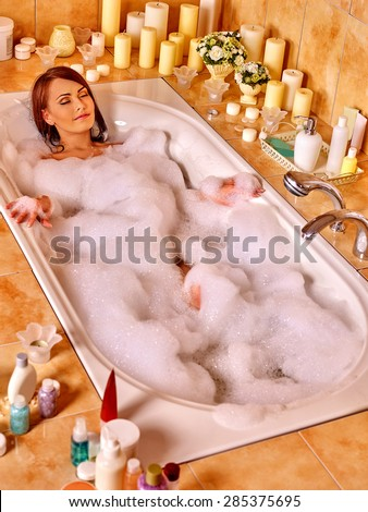 Woman relaxing at water in bubble bath. Top view. - stock photo