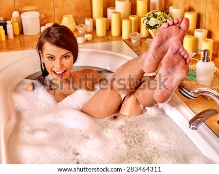 Woman relaxing at water in bubble bath. Visible bare feet. - stock photo
