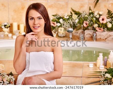 Woman relaxing at water spa. Girl sitting near a bath tub - stock photo