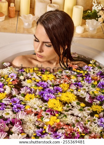Woman relaxing at water spa. Many flowers in  bathroom