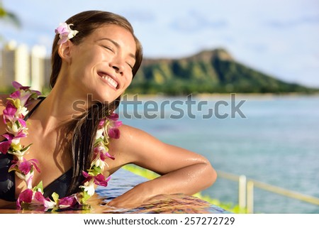 woman relaxing enjoying sun at pool resort. Peaceful young lady with closed eyes feeling the sun rays on her skin during suntan in infinity pool at beach hotel in Waikiki, Honolulu, Hawaii. - stock photo