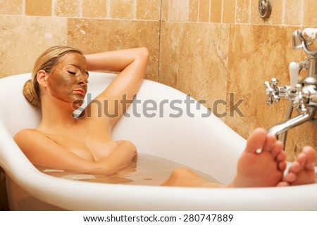 Woman relaxing in a bath with chocolate mask on her face. - stock photo
