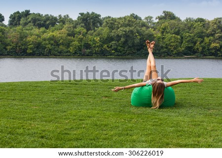 Woman relaxing in a chair on the grass near river - stock photo