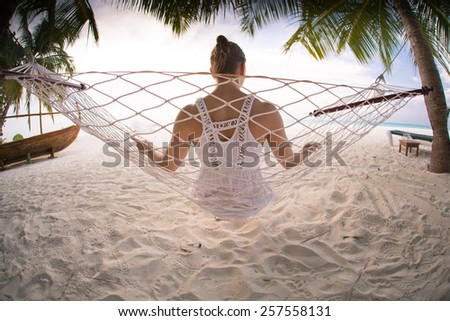 woman relaxing in a hammock at a beach in the sun on a maldivian island - stock photo