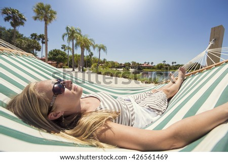 Woman relaxing in a hammock while on vacation  - stock photo