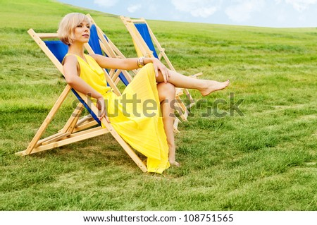 Woman relaxing in a lounge chair - stock photo