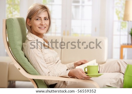 Woman relaxing in armchair at home, reading book , holding coffee cup. - stock photo