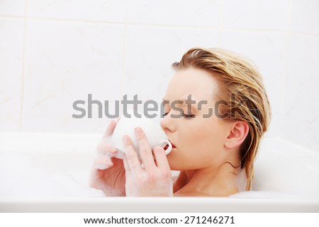 Woman relaxing in bath, drinking cup of coffee. - stock photo