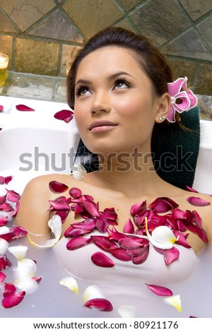 Woman relaxing in bath with plumeria petal - stock photo
