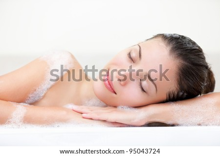 woman relaxing in bath with serene smile and closed eyes with bath foam. Beautiful young multiracial Caucasian / Asian Chinese female model. - stock photo