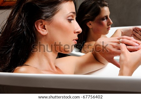 Woman relaxing in bathtub with mirror image of her with bruises on her face, a conceptual shoot of domestic abuse often hidden from public - stock photo