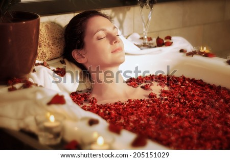 Woman relaxing in bathtub with rose blossoms - stock photo