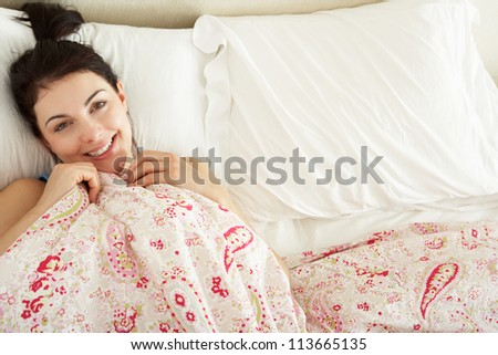 Woman Relaxing In Bed - stock photo