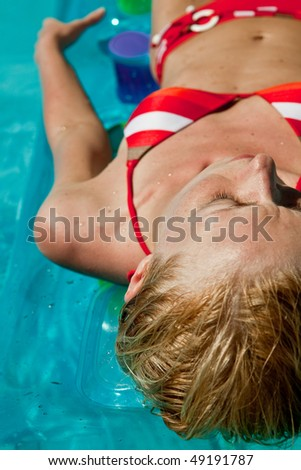 Woman relaxing in blue outdoor swimming waterpool - stock photo
