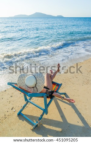 Woman relaxing in deck chair on the beach on a sunny day - stock photo