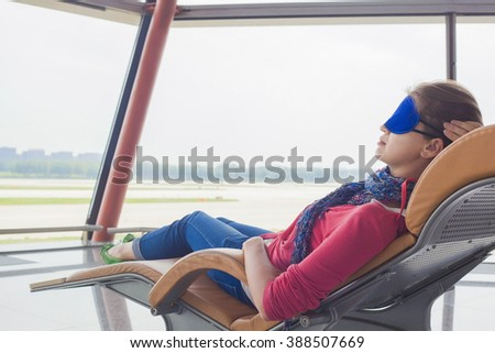 woman relaxing in eye sleep mask at airport terminal awaiting the flight. transportation concept - stock photo