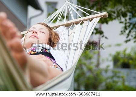 Woman relaxing in hammock in the garden - stock photo